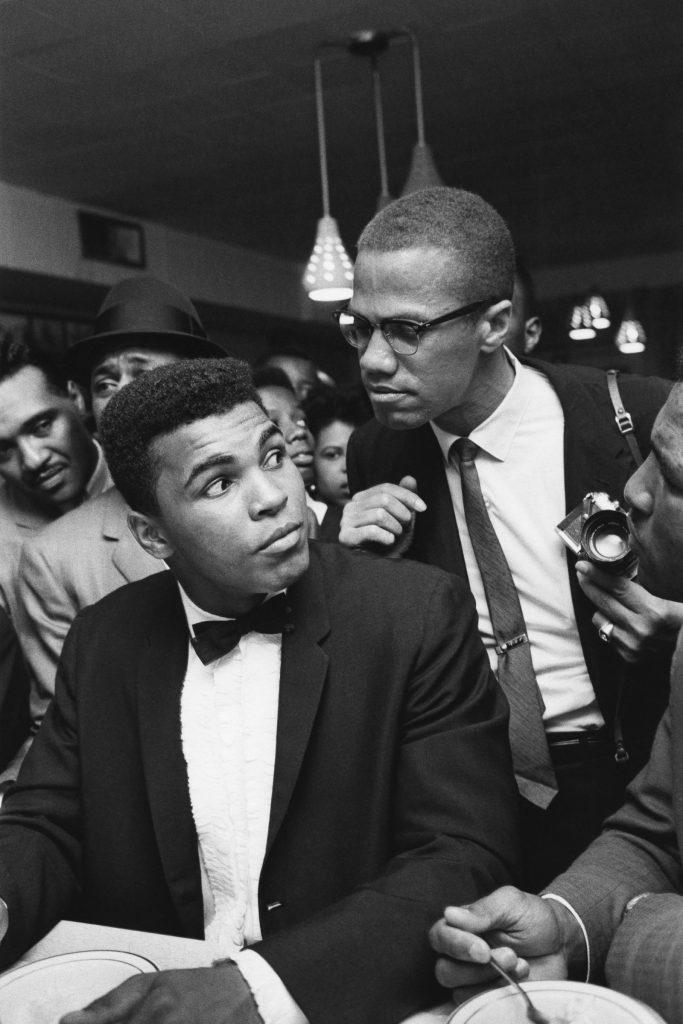 1964. Cassius Clay, campione del mondo dopo aver sconfitto Sonny Liston, con Malcom X, ministro della Nation of Islam, poco prima dell'annuncio della conversione e dell'adozione del nome Muhammad Ali. Bob Gomel/Sygma/Getty Images